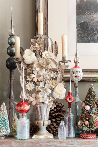 Holiday vignette with vintage blown-glass tree toppers in old bottles, retro-style small decorative Christmas trees, and a Tole candleholder fashioned to look like a vase of cream-colored flowers in the home of event planners Rick Davis and Christopher Vazquez