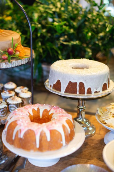 A variety of cakes and sweets on tiered trays and cake plates
