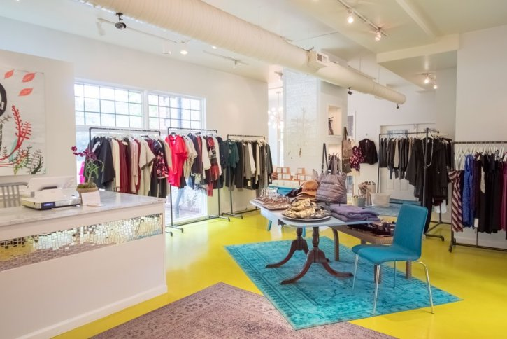 Scout Boutique's light and bright interior with painted yellow floors, turquoise and neutral oriental rungs, an antique pedestal dining table holding folded cloths, and long free-standing racks of clothes around the perimeter