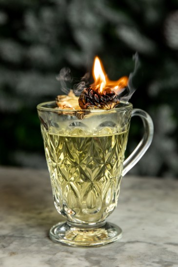 Dalloway Terrace's hot toddy is served in a crystal cup with a pedestal and handle. The herb garnish is set aflame for a wintry presentation