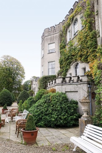 Vacationing in Ireland: View of Glin Castle's crenellated exterior, partially covered in climbing vines and bordered by green shrubs. At the base of the shrubs, ample benches for houseguests face out toward the garden view.