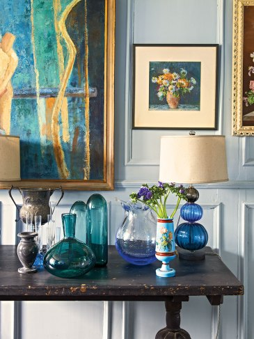 English country house interiors: a vignette of vintage glass and pewter vases on worn, dark wood table, with plentiful art, both modern and traditional, hanging on the pale gray walls behind