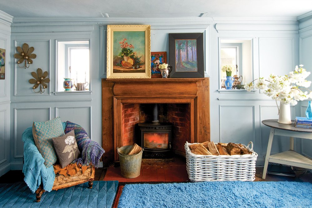 In Nikki Tibbles' 1760 English country home, a fireplace with a warm-colored natural wood surround and mantle contrasts with pale blue-gray room (painted Farrow & Ball 'Parma Gray' wall). She has decorated the room with two solid bright blue plush rugs in contrasting textures, framed paintings, vintage vases, and a chair piled with throw pillows and cozy throws in cool colors. On a table to the right side of the room, large white enamel pitcher holds cut branches covered in white fluffy flowers. A large white basket holds chopped wood beside the fireplace.