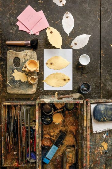 leaf cutouts and artist tools, including a palette, brushes and cups of paint