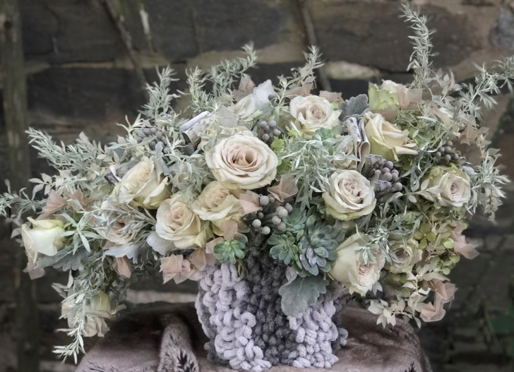 a floral arrangement featuring silvery foliage, muted roses, succulents, and a woven base in pale and charcoal grey yarn
