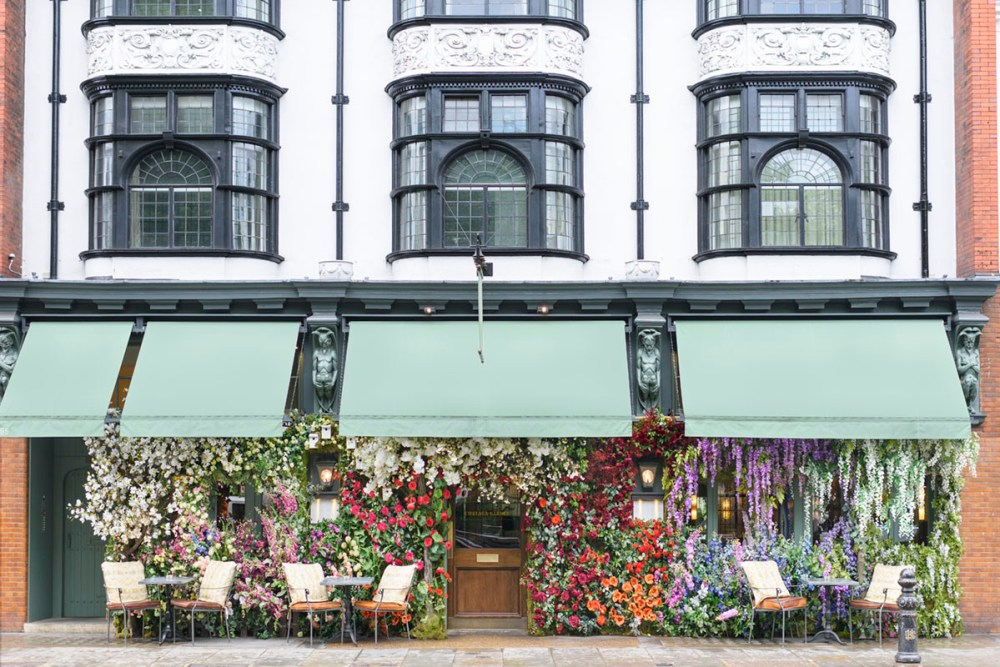 Beneath a green awning, the Ivy restaurant storefront is covered in colorful, lush blooms. Above, ornate windows overlook the London street scene