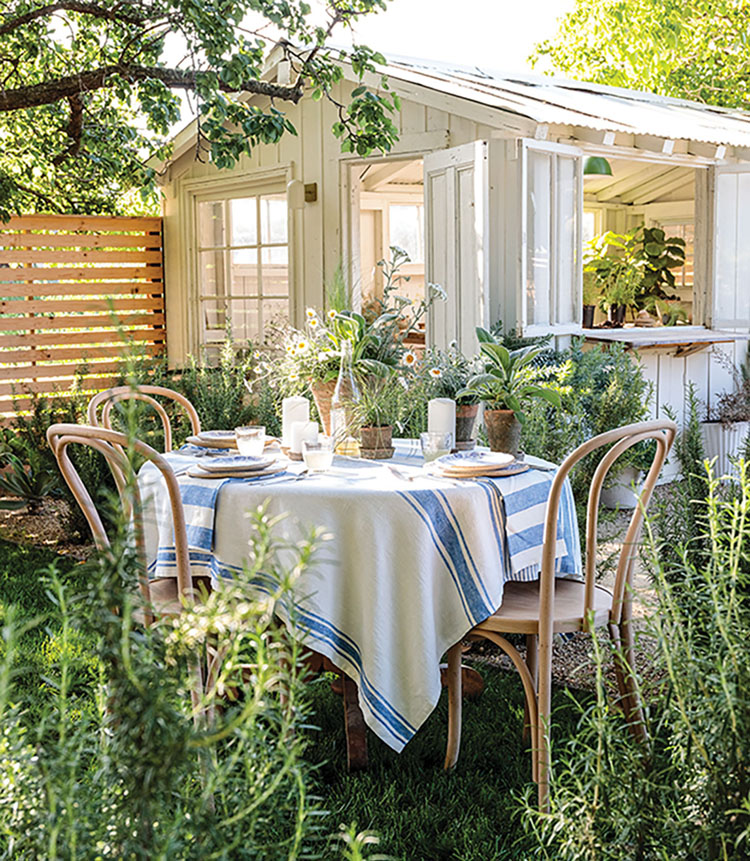 A centerpiece of potted plants on an alfresco table, nestled among rosemary in a California garden, beside a quaint white potting shed.