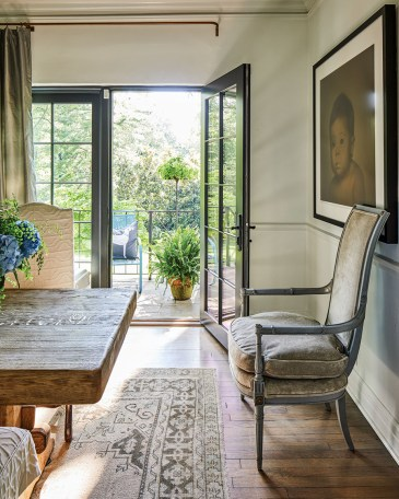 A view of Lorie and Gavin Duke's dining room looking out onto French doors and patio. One door is open and sunlight streams in.