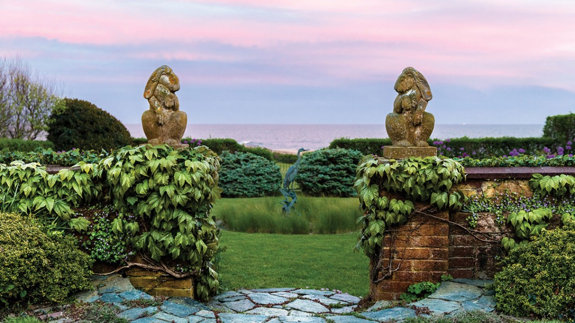 A glimpse of the Newport, RI, coast through the walled garden entrance of Oatsie Charles's home, The Whim