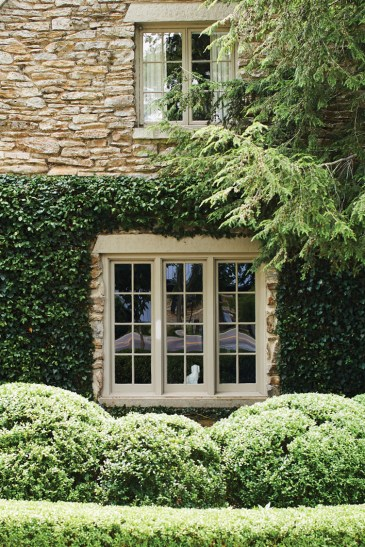 mullioned window surrounded by boxwoods, climbing vines, and overhanging branches