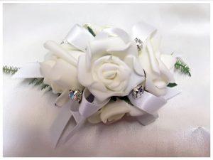 White roses, antique satin ribbon and diamantes' throughout.