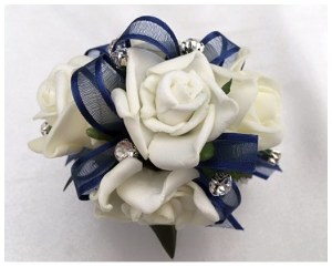 White roses, navy organza/satin trim ribbon, diamantes added.