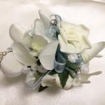White roses and orchid mix, pale blue organza ribbon, baby's breath and diamantes added.