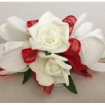 Orchid and rose mix with red organza ribbon.