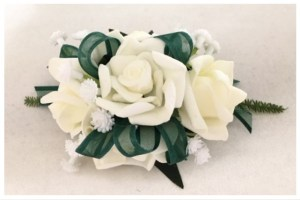 White rose wrist corsage with dark green organza ribbon and added baby's breath.