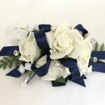 White roses, silver diamante`s, baby's breath, navy satin ribbon wrist corsage.