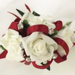 White roses, dark red ribbon, silver diamante`s.
