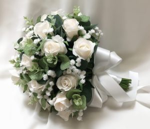 Bridal posy with cream roses, gum leaves, baby's breath and satin bow and tails.