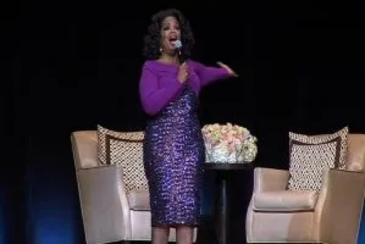 Oprah Winfrey on stage beside floral arrangement