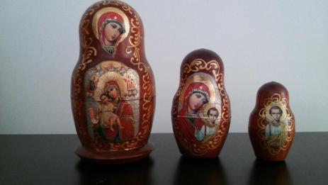 """This version of a Russian matryoshka nesting doll was purchased in Moscow, when I traveled there for a presentation in 2010. The innermost doll is a Christ child, appropriately nestled within the body of the larger dolls with the Virgin Mary on them. The larger two dolls have different icons of the Virgin on them. As I was shopping in a market, browsing various matryoshka dolls (including one with the 4 Beatles, one with various Russian and U.S. leaders, and one, which I gave to my sister, which had versions of Michael Jackson on each doll), the man who owned the stall heard me coughing. He urged me to buy this doll, since, he told me, """"She is good for [cough, cough],"""" and patted his chest."""