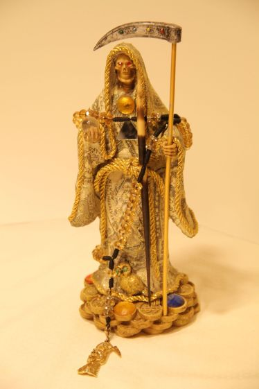 La Huesuda–Santa Muerte Statuette (Early 2000s) Los Angeles, California. Artist Unknown. (Resin, paper, mirrors, wood, paste gems, beads, twine, metal charms, rice, seeds, rose petals)(12 x 5 x 4)
