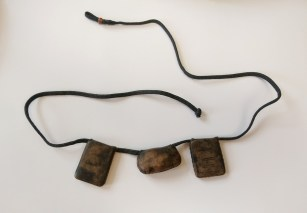 "Leather amulet. Purchased in the old city market of Kano, Nigeria in 1990. Leather, thread, braided cord, wooden bead, unknown internal materials. Cord: 28"", outer bundles 1.5"" x 1"" x .25"", middle bundle .75"" x 1.5"" x .5"""