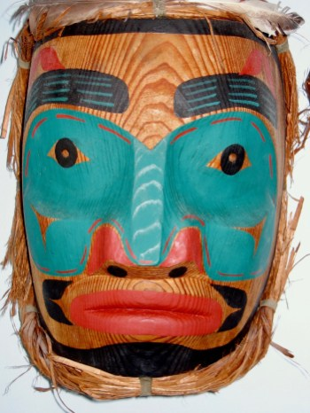 "Hand carved by First Nations artist, Veronica Hackett Campbell River, BC 1992 Wood, raffia, feathers 12"" x 9"""