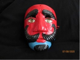 Hard carved wooden mask, 9 x 7 inches, red face with blue chin, impressive mustache, and eyebrows. His eyes have eyelashes possibly of horsehair. The mask's eyeholes are above the painted eyes, and just below the eyebrows. A very handsome shepherd indeed.