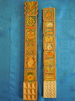 Two unusual Mongolian wooden tsatsals with carved-and-painted traditional Buddhist symbols, as well as animals associated with the Mongolian twelve-year calendar cycle and depictions of mountains, flowers, grass, the sun, and the crescent moon. Some of the paint on the larger tsatsal is also lightly gilded. The three-by-three grid pattern of the smaller tsatsal is carved with four indentations inside each of the nine squares, making 36 hollows to hold the milk, thus multiplying the strength and effectiveness of the milk offering when it is tossed into the air. Purchased: Ulaanbaatar, Mongolia, 2008. Materials: Wood, paint. Dimensions: 16 inches long (left), 14-1/2 inches long (right).