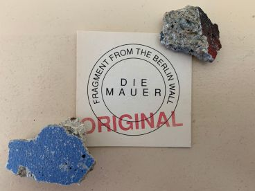 I studied in Germany for 18 months ending in July of 1989. When I departed, no one seemed to have any inkling that the East German revolution would bring down the Berlin Wall just a few months later. My friend Joachim in Berlin went out and gathered small bits of the breached barrier to share with me. I placed these two pieces in a case with certificate I purchased in Berlin some time later. The paint and composition of the Wall fragments in that case revealed that they clearly were not genuine despite the claim. As an artifact itself, however, the certificate and its English text reveal the interest tourists have in connecting with true history. I end this presentation with these Wall fragments as a reminder that social change can come peacefully and unexpectedly. Though few suspected the imminent end to the East German regime in the summer of 1989, people committed to greater freedom continued their efforts. Those efforts in East Germany eventually led to a true revolution without the loss of a single life.