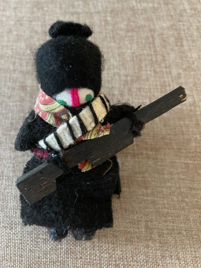 I have a collection of odd dolls including a quinceañera doll that is in my archives at the University of Texas at San Antonio. To share here I chose two that are on my bookshelves: the Zapatista doll that a friend brought me from Chiapas about 20 years ago. The Zapatista is about 5 inches tall and made with what appear to be scraps of fabric and a wooden rifle.