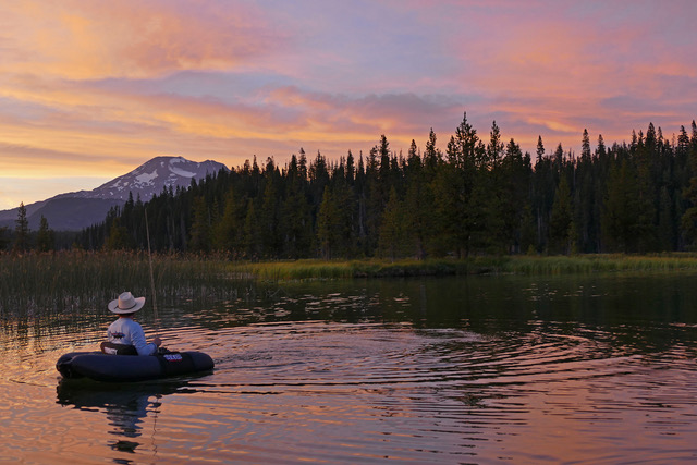 a fly fisher on hosmer lake in Oregon at sunset