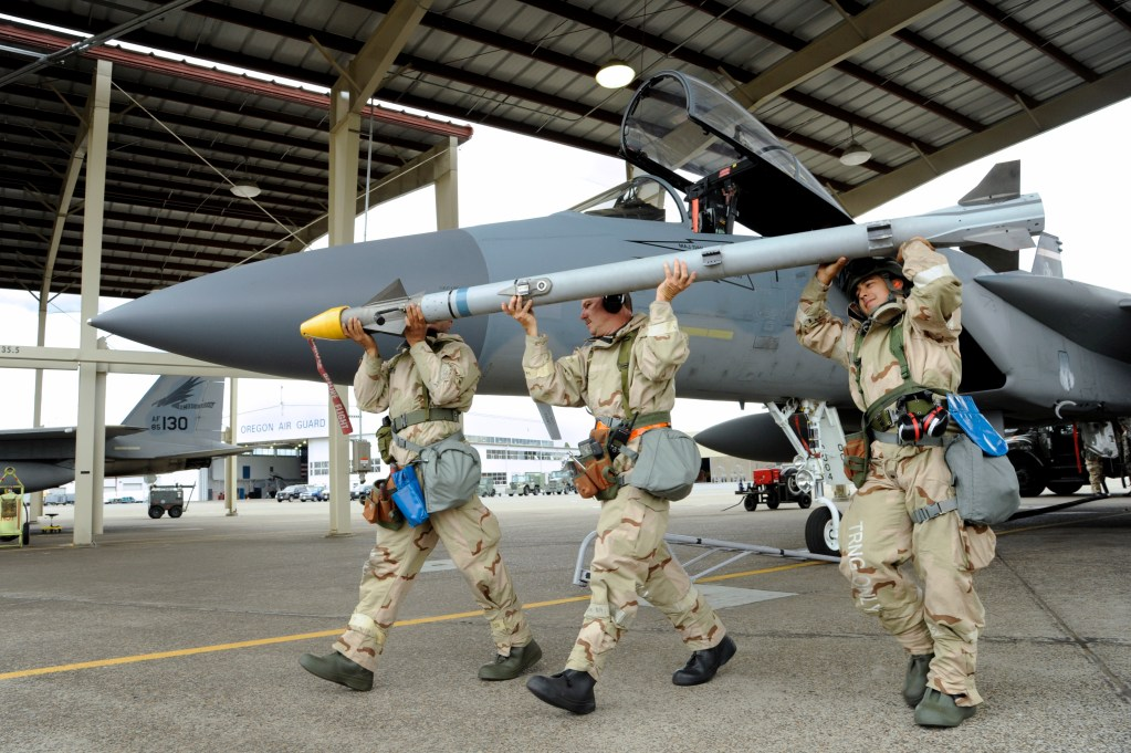 Oregon Air National Guard Senior Airman Nelson Chicas-Ramos (right) along with Master Sgt. Michael Boudreau (center) and Staff Sgt. Bryce Cunningham (left) remove a training missiles from a F-15C Eagle assigned to the 142nd Fighter Wing, Portland Air National Guard Base, Oregon, after an afternoon sortie as part of combat readiness training, Sept. 8, 2018. (U.S. Air National Guard photo by Master Sgt. John Hughel, 142nd Fighter Wing