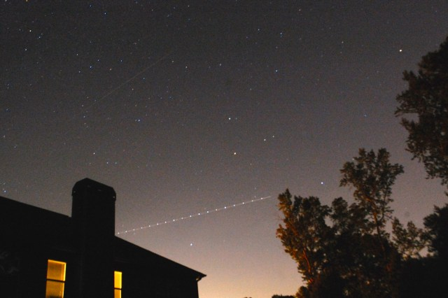 The meteor is the faint streak of light above the chimney.