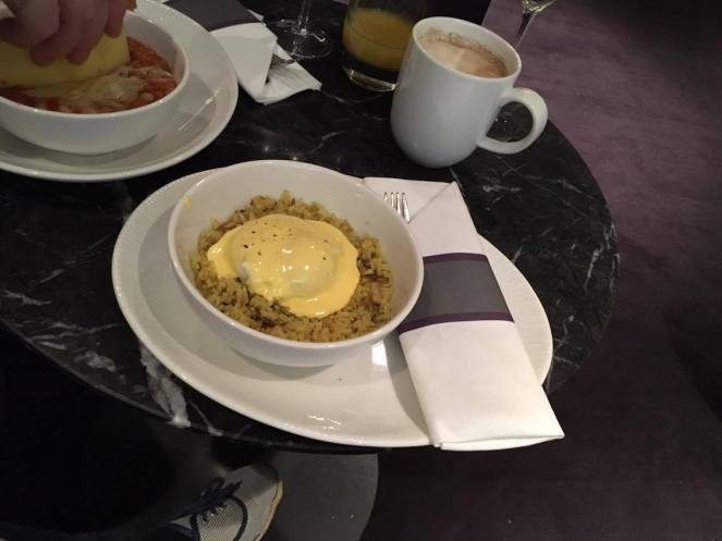 a bowl of kedgeree on a black marble table in the No1 Traveller Lounge Gatwick North terminal