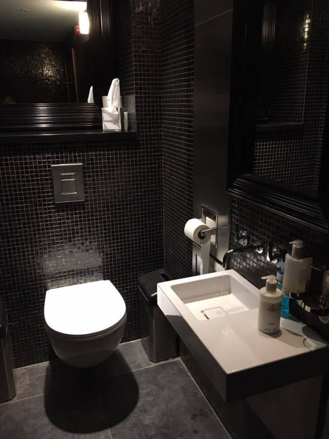 a black tiled bathroom in the No1 Traveller Lounge Gatwick North terminal