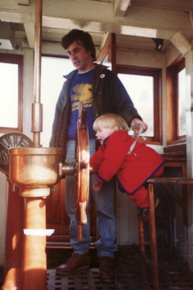 Rosie as a toddler, wearing a red coat and reins, held up by her dad, to a wooden boat wheel