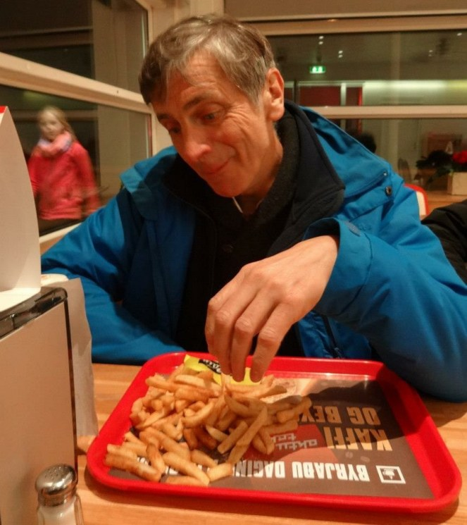Jonathan eats chips from a red tray in Aktu Taktu in Iceland