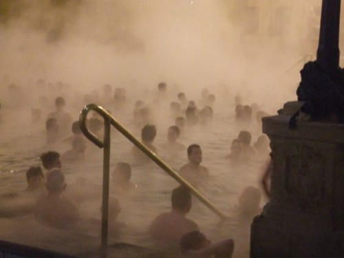 A photo showing the steps into the main pool of the Széchenyi Baths steaming at night with lots of people
