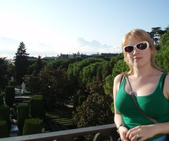Rosie wearing a green strap top and sunglasses by a wall overlooking gardens in Madrid, Spain