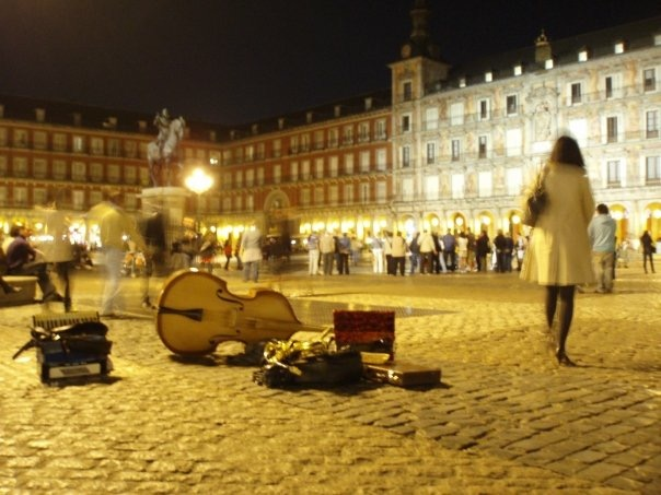 Instruments from street performers sit on the cobbles of Plaza Mayor at night in Madrid, Spain