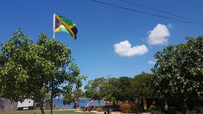The Jamaican flag flies in a blue sky above Jack Sprats bar in Treasure Beach, Jamaica