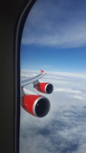 A view from the window of 2 red engines a the wing of a Virgin Atlantic Boeing 747 plane