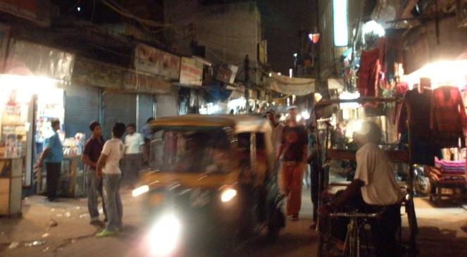 A cycle rickshaw and a tuk tuk amongst people walking on Paharganj, Delhi, India at night