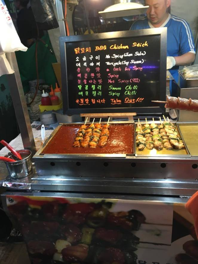 a street food stall with black menu board and neon writing, selling chicken sticks in Seoul, South Korea