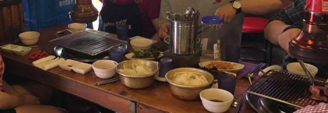 several bowls of food and 2 grills built into a table in a restaurant in Seoul, South Korea