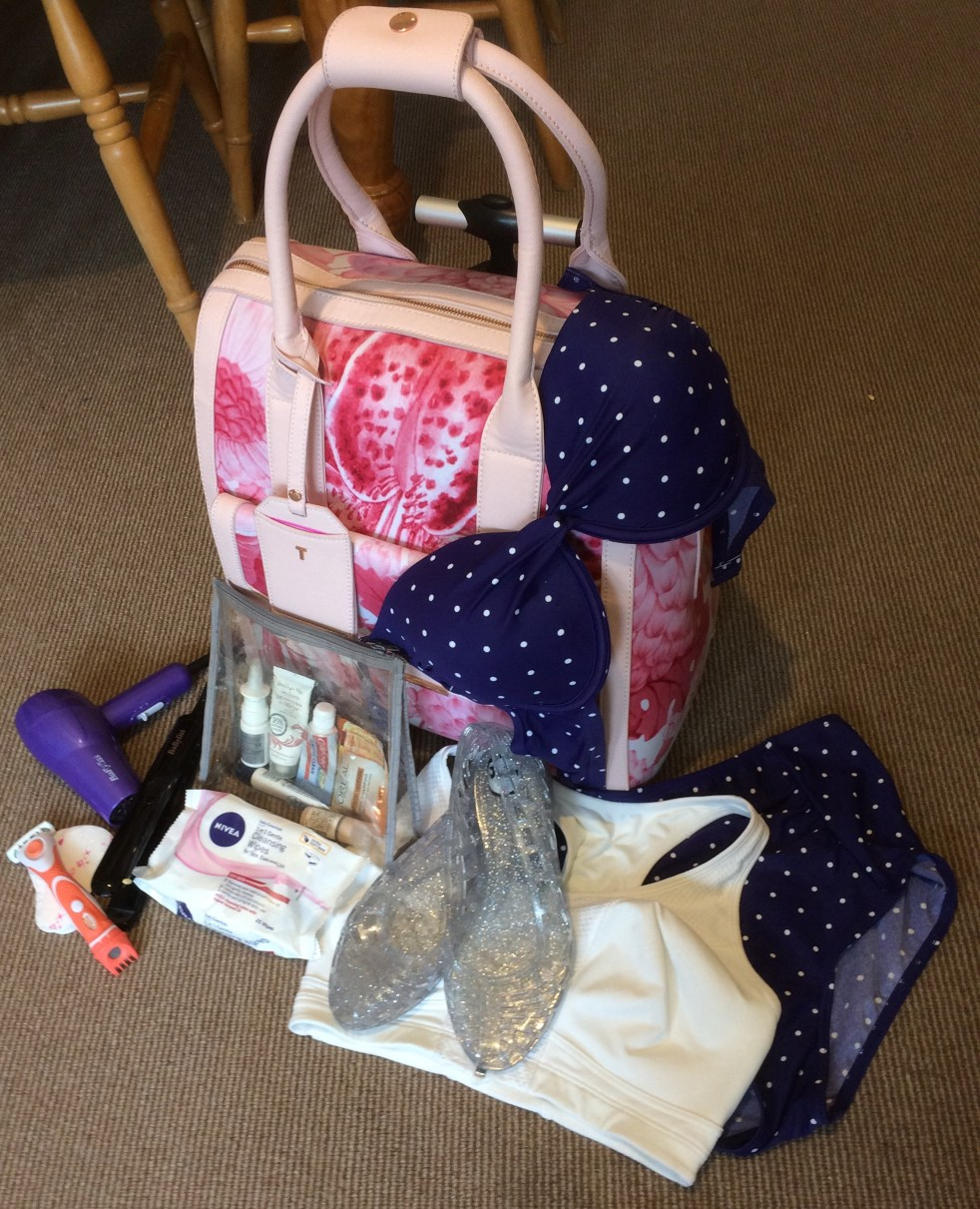 photo of a pink travel bag with blue polka bikini, white sports bra, clear make up bag, small purple hairdryer, wet wipes and razor