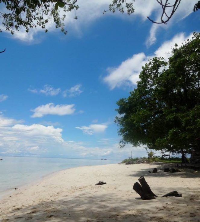 a white sandy beach and blue sky dotted with clouds in Thailand
