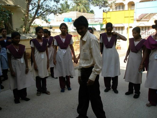 A teenage Indian schoolboy in the centre of a circle of teenage schoolgirls dancing in Kolar Gold Fields