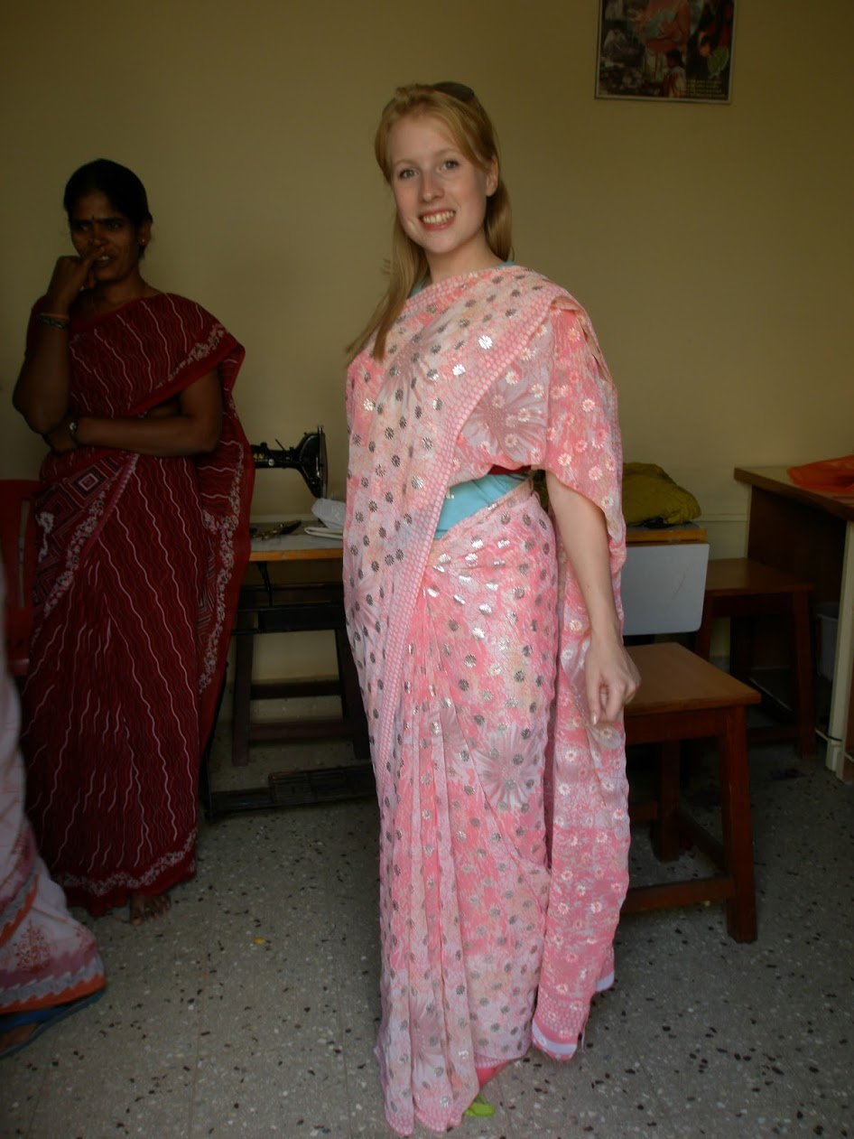 Rosie smiling for a photo in a pink and silver sari